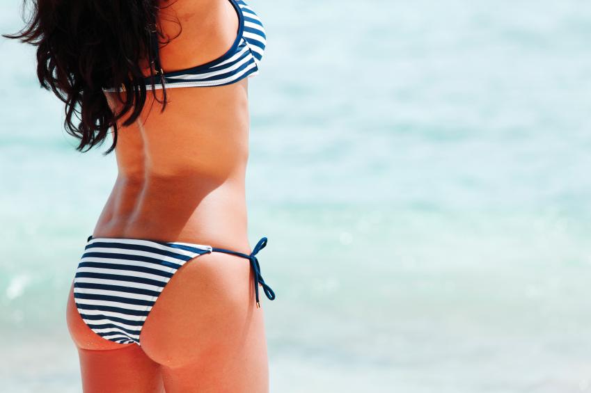 Sexy back of a beautiful woman in bikini on sea background