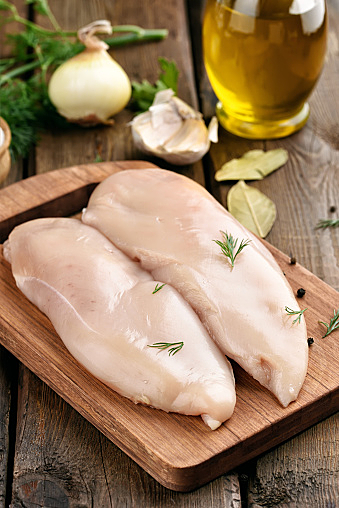 Raw chicken meat on cutting board