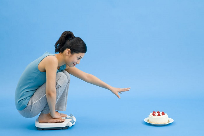 43727205 - woman on a weight scale trying to get the cake