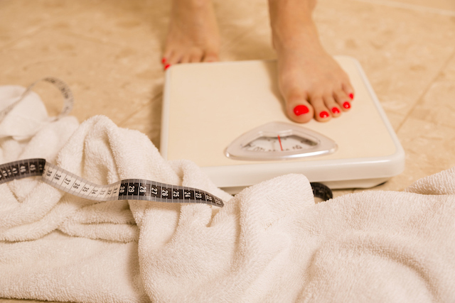 Health conscious woman standing on bathroom scale. Her towel and tape measure are on the tile floor by the scale.